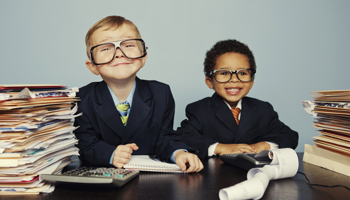 two young kids dressed in business suits at a desk with papers