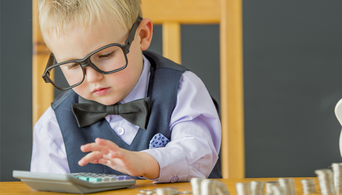 young kid dressed in business clothes using a calculator