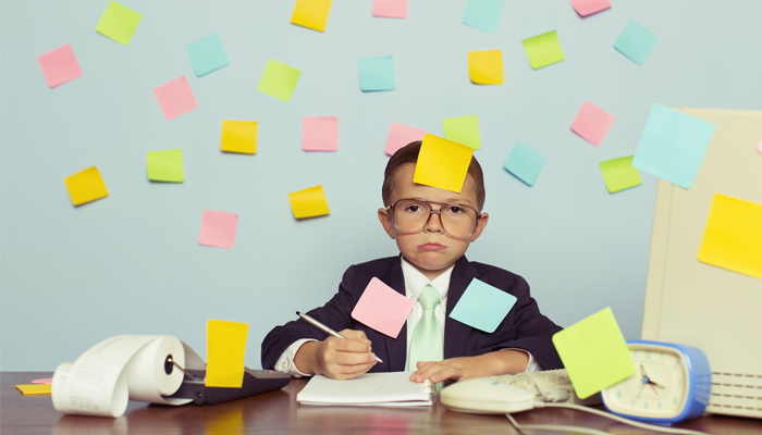 young kid in business suit sitting at desk covered in sticky notes