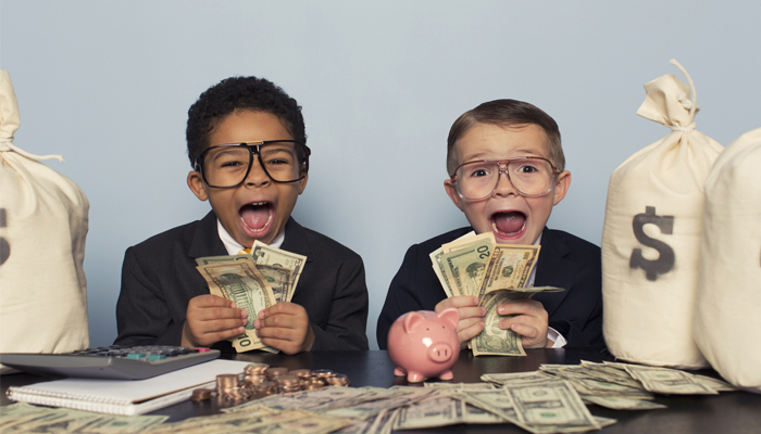 two young kids in business suits counting stacks of money from money bags