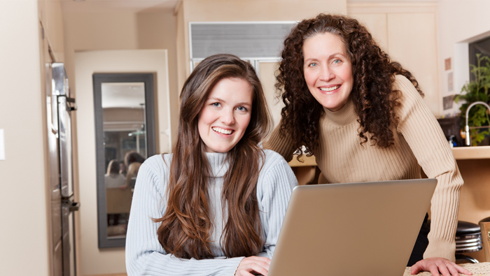 A mother and daughter working at computer together