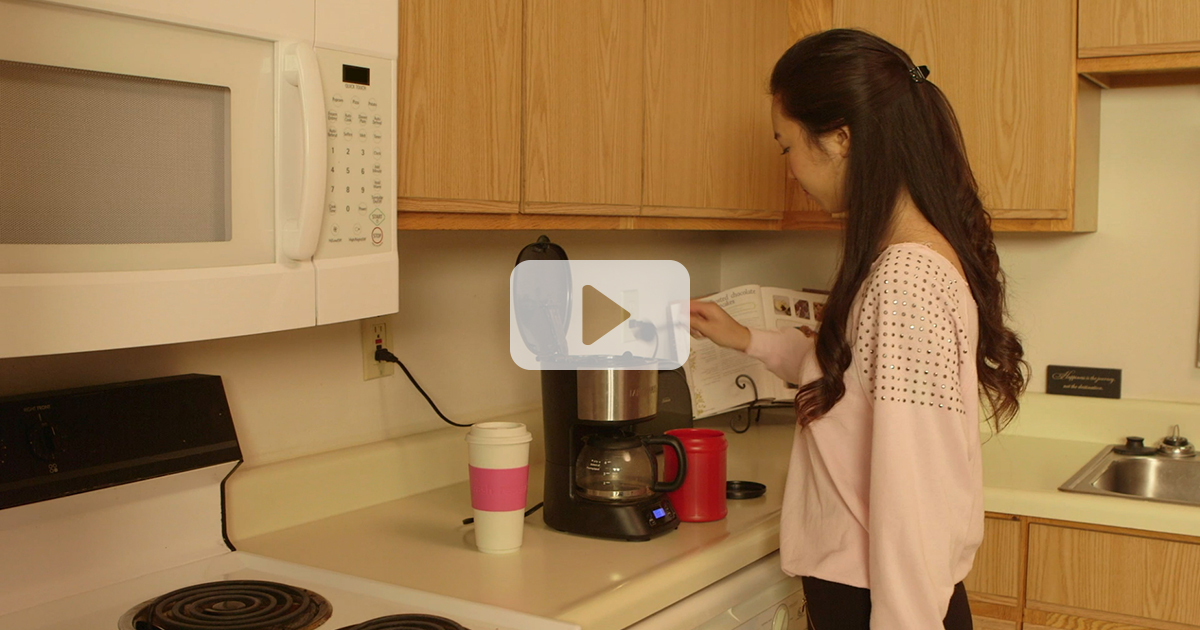 screenshot from video, young woman making coffee